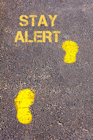stay alert: Yellow footsteps on sidewalk towards Stay Alert message.Conceptual image