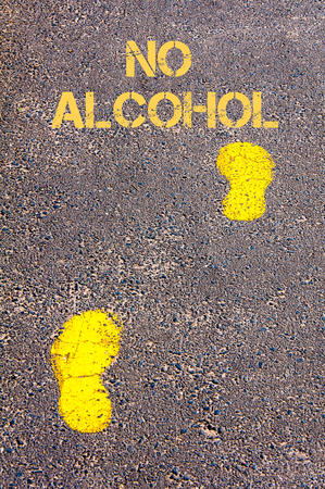 no alcohol: Yellow footsteps on sidewalk towards No Alcohol message.Conceptual image