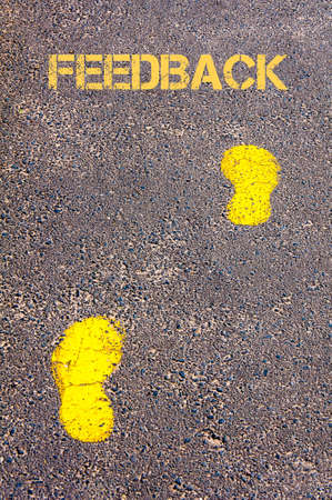 criticize: Yellow footsteps on sidewalk towards Feedback message.Conceptual image