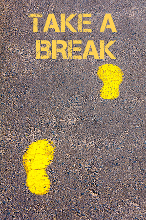 take a break: Yellow footsteps on sidewalk towards Take a break message.Conceptual image Stock Photo