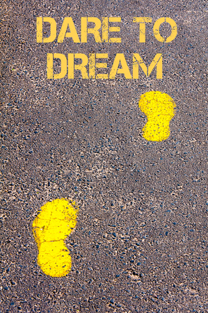 dare: Yellow footsteps on sidewalk towards Dare to Dream message.Concept image