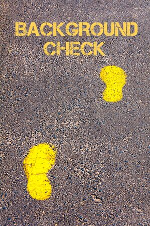 background check: Yellow footsteps on sidewalk towards Background Check message.Concept image