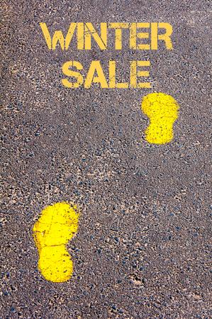 sidewalk sale: Yellow footsteps on sidewalk towards Winter Sale message.Conceptual image