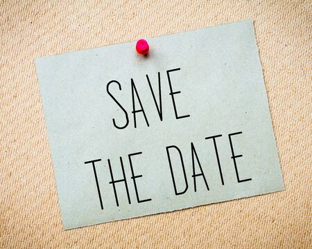image date: Recycled paper note pinned on cork board.Save the Date Message. Wedding Concept Image