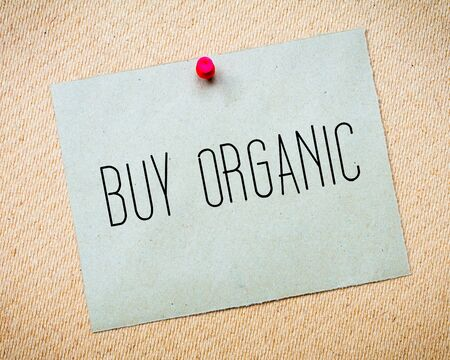 billboard posting: Recycled paper note pinned on cork board.Buy Organic Message. Concept Image