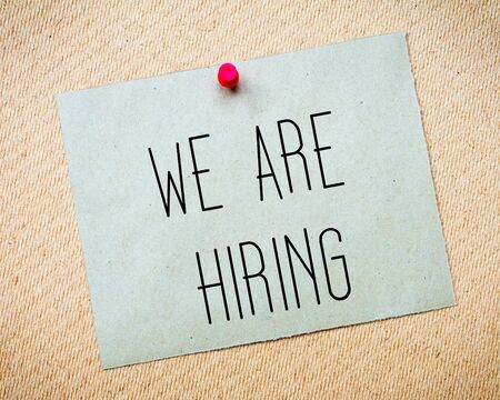 billboard posting: Recycled paper note pinned on cork board.We are hiring Message. Concept Image