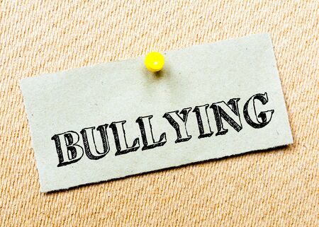 billboard posting: Recycled paper note pinned on cork board. Bullying Message. Concept Image