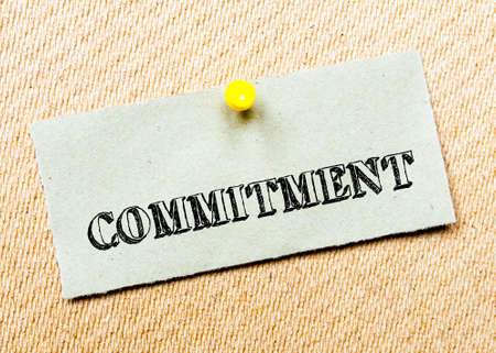 billboard posting: Recycled paper note pinned on cork board.Commitment Message. Concept Image