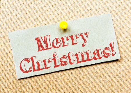 billboard posting: Recycled paper note pinned on cork board. Merry Christmas Message. Concept Image