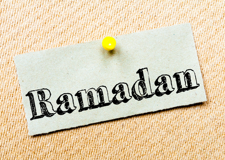 billboard posting: Recycled paper note pinned on cork board. Ramadan Message. Concept Image Stock Photo