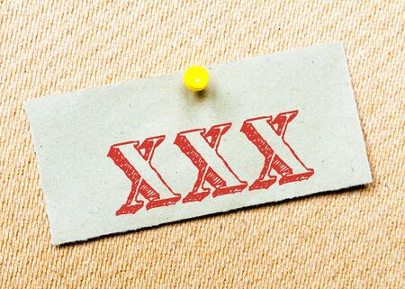 xxx: Recycled paper note pinned on cork board. XXX Message. Concept Image