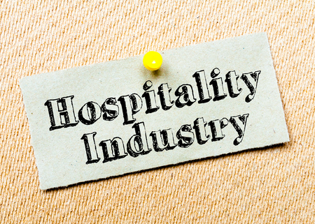 Recycled paper note pinned on cork board. Hospitality Industry Message. Concept Image Stock Photo