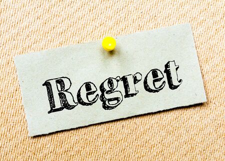 Recycled paper note pinned on cork board. Regret Message. Concept Image Stock Photo