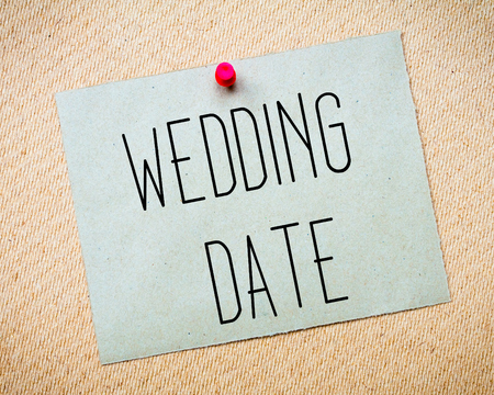 billboard posting: Recycled paper note pinned on cork board. Wedding Date Message. Concept Image