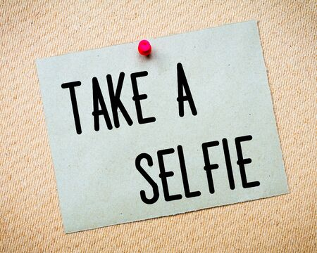 take a note: Recycled paper note pinned on cork board. Take a Selfie Message. Concept Image