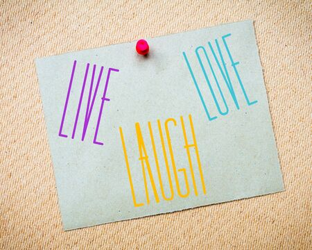 billboard posting: Recycled paper note pinned on cork board. Live Laugh Love Message. Concept Image