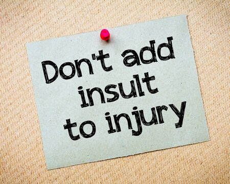 insult: Dont add insult to injury Message. Recycled paper note pinned on cork board. Concept Image Stock Photo
