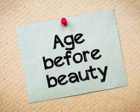 idioms: Age before beauty Message. Recycled paper note pinned on cork board. Concept Image Stock Photo