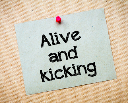alive: Alive and kicking Message. Recycled paper note pinned on cork board. Concept Image Stock Photo