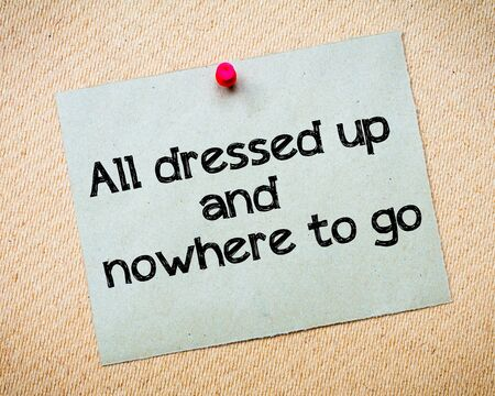 idioms: All dressed up and nowhere to go Message. Recycled paper note pinned on cork board. Concept Image Stock Photo
