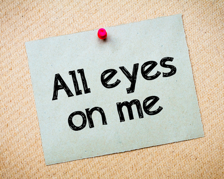 idioms: All eyes on me Message. Recycled paper note pinned on cork board. Concept Image Stock Photo