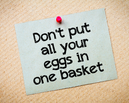 all one: Dont put all your eggs in one basket Message. Recycled paper note pinned on cork board. Concept Image