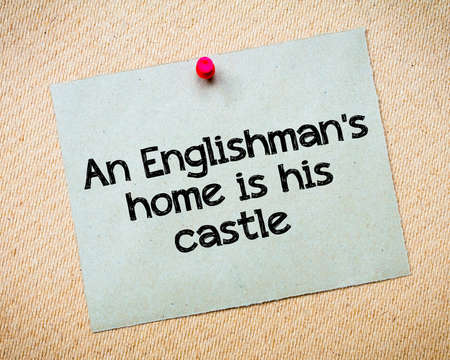 englishman: An Englishmans home is his castle Message. Recycled paper note pinned on cork board. Concept Image