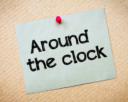 idioms: Around the clock Message. Recycled paper note pinned on cork board. Concept Image