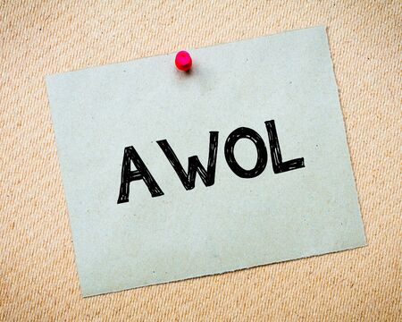 AWOL - Absent Without Official Leave Message. Recycled paper note pinned on cork board. Concept Image
