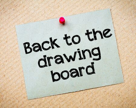 idioms: Back to the drawing board Message. Recycled paper note pinned on cork board. Concept Image Stock Photo