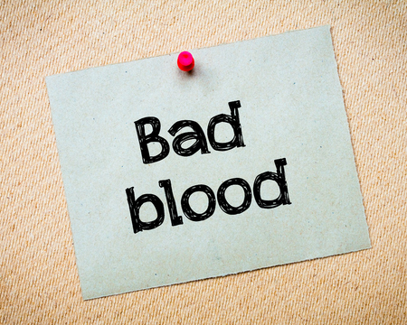 idioms: Bad Blood Message. Recycled paper note pinned on cork board. Concept Image