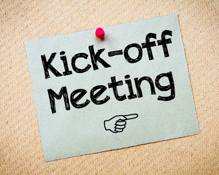 kickoff: Kick-off meeting Message. Recycled paper note pinned on cork board. Concept Image