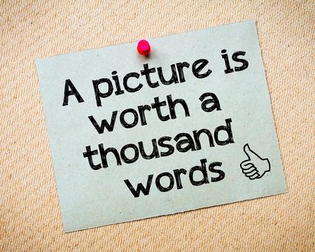 valor: Una imagen vale m�s que mil palabras un mensaje. Reciclado nota de papel clavado en tarjeta del corcho. Concepto de imagen Foto de archivo
