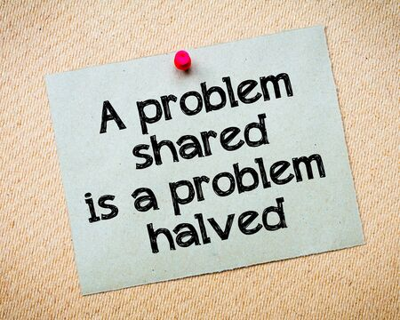 idioms: A problem shared is a problem halved Message. Recycled paper note pinned on cork board. Concept Image