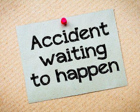 idioms: Accident waiting to happen Message. Recycled paper note pinned on cork board. Concept Image