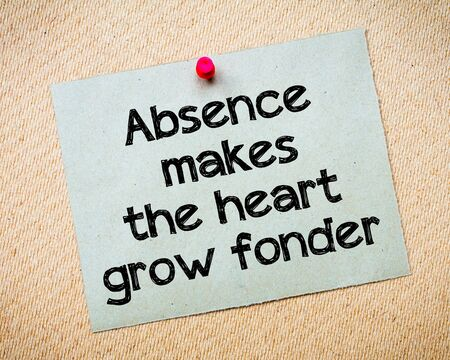 Absence makes the heart grow fonder Message. Recycled paper note pinned on cork board. Concept Image Stock Photo