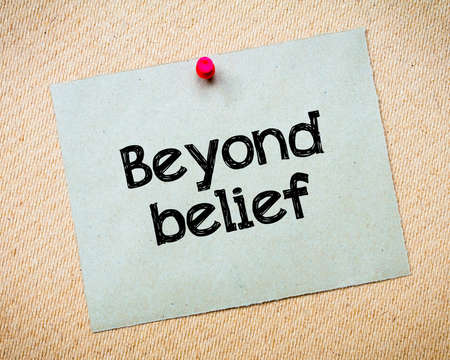 beyond: Beyond belief Message. Recycled paper note pinned on cork board. Concept Image