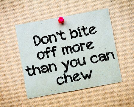 than: Dont bite off more than you can chew Message. Recycled paper note pinned on cork board. Concept Image Stock Photo