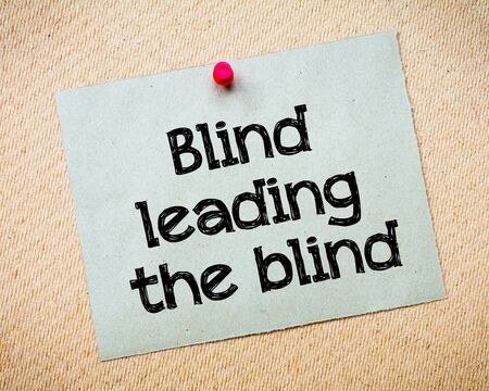 leading: Blind leading the blind Message. Recycled paper note pinned on cork board. Concept Image