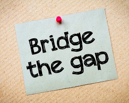 bridge the gap: Bridge the gap Message. Recycled paper note pinned on cork board. Concept Image Stock Photo