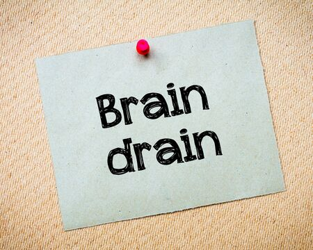 idioms: Brain drain Message. Recycled paper note pinned on cork board. Concept Image