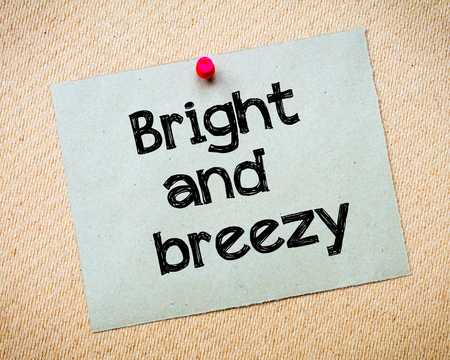 breezy: Bright and breezy Message. Recycled paper note pinned on cork board. Concept Image
