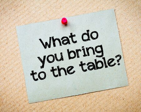 What do you bring to the table? Message. Recycled paper note pinned on cork board. Concept Image