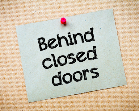 idioms: Behind closed doors Message. Recycled paper note pinned on cork board. Concept Image