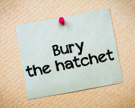 bury: Bury the hatchet Message. Recycled paper note pinned on cork board. Concept Image Stock Photo