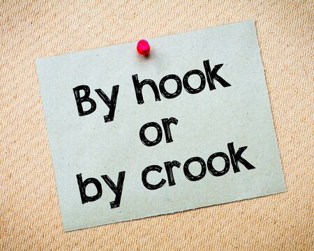crook: By hook or by crook Message. Recycled paper note pinned on cork board. Concept Image