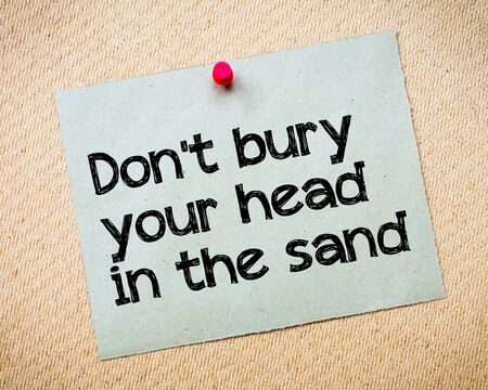 bury: Dont bury your head in the sand Message. Recycled paper note pinned on cork board. Concept Image