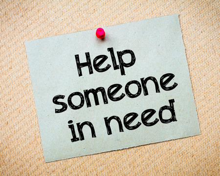 someone: Help someone in need Message. Recycled paper note pinned on cork board. Concept Image