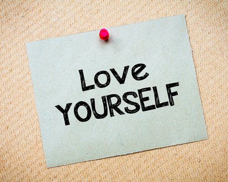 idioms: Love yourself Message. Recycled paper note pinned on cork board. Concept Image Stock Photo