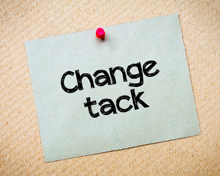 tack: Change Tack Message. Recycled paper note pinned on cork board. Concept Image